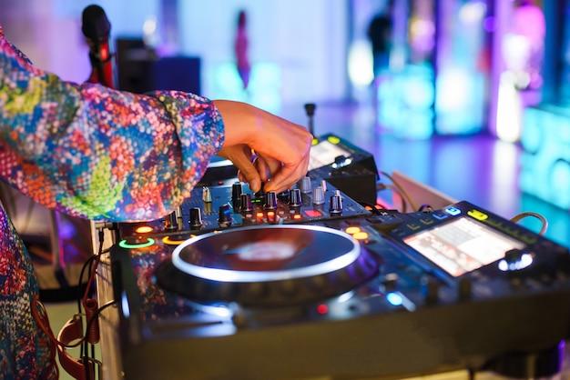 Jonge sexy vrouwelijke dj mengt muziek