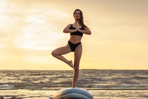 Jonge sexy vrouwensurfer die op haar supraad op de zonsondergang mediteren.