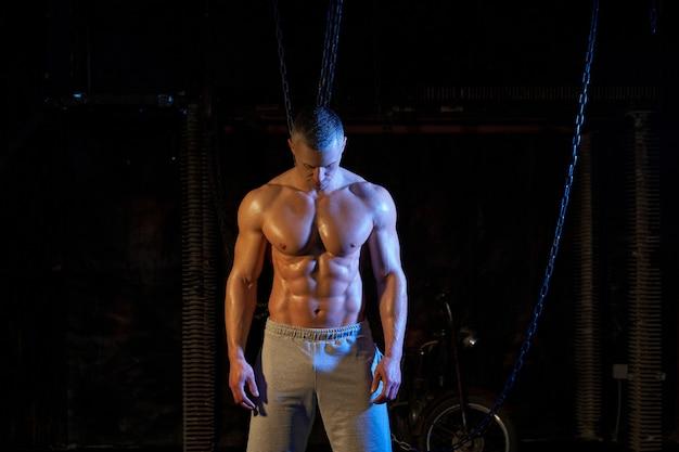 Jonge shirtless gespierde man die tussen metalen kettingen staat, serieus naar de camera kijkt, ruimte kopieert met zijn rug naar de camera toont biceps