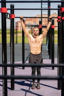 Jonge shirtless gespierde sportman die door bars van sportfaciliteiten houdt alvorens oefening op zomerdag te doen