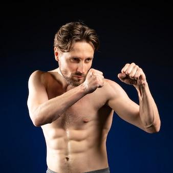 Jonge shirtloze atletische man die vecht