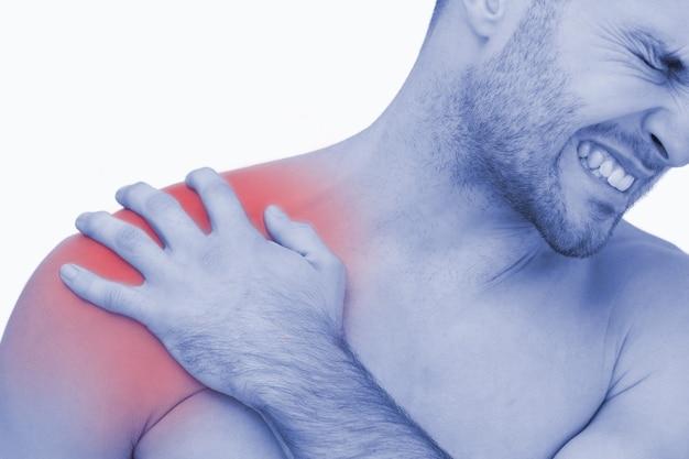 Jonge shirtloze man met schouderpijn