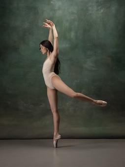 Jonge sierlijke tedere ballerina op donkergroen