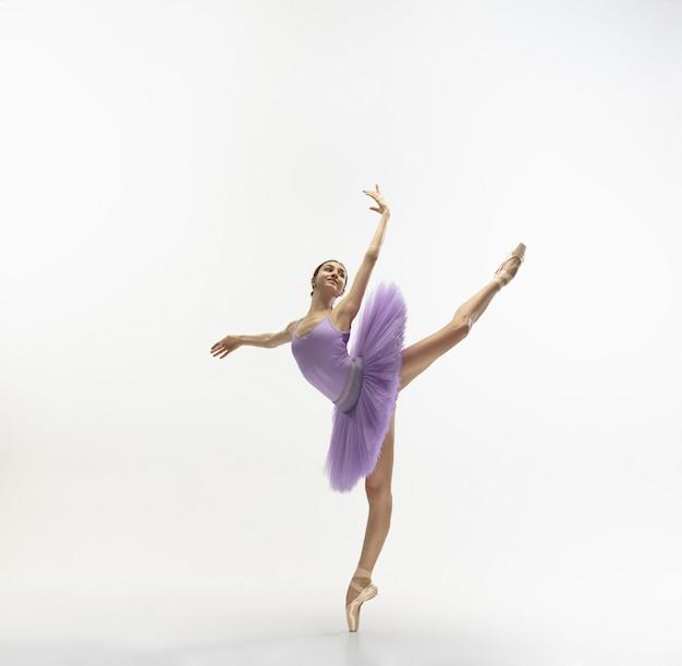 Jonge sierlijke tedere ballerina op witte muur