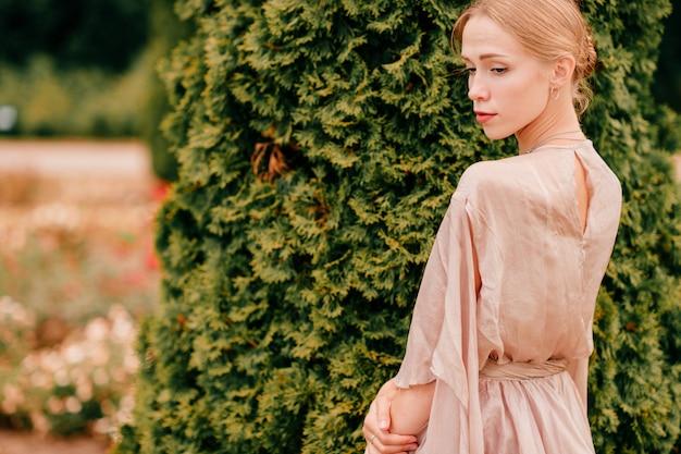 Jonge sierlijke vrouwelijke balletdanser in theatrale jurk poseren in zonnig park