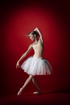Jonge sierlijke vrouwelijke balletdanser of klassieke ballerina dansen op rode studio. kaukasisch model op pointeschoenen
