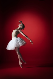 Jonge sierlijke vrouwelijke balletdanser of klassieke ballerina dansen op rode studio.