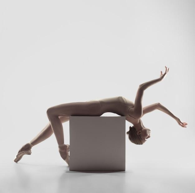 Jonge sierlijke vrouwelijke balletdanser of klassieke ballerina dansen op witte studio. kaukasisch model op spitzen