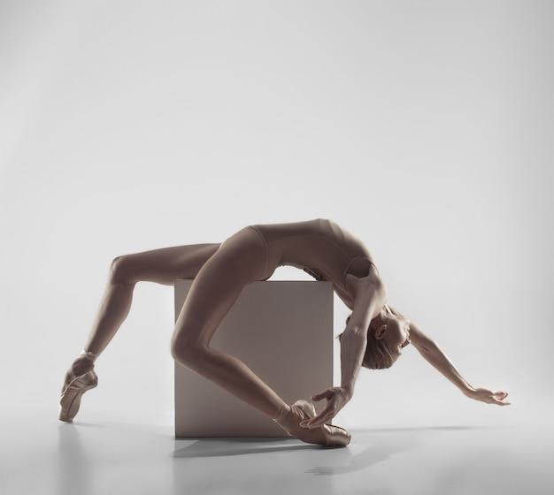 Jonge sierlijke vrouwelijke balletdanser of klassieke ballerina dansen op witte studio.