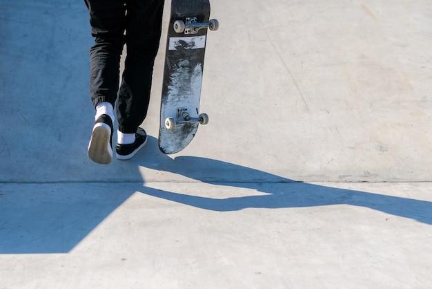 Jonge skateboardatleet die de oprit oploopt terwijl hij een skateboard vasthoudt.