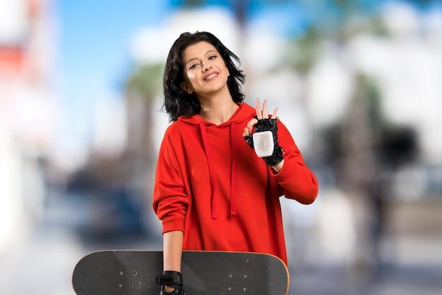 Jonge skatervrouw die ok teken met vingers toont in openlucht