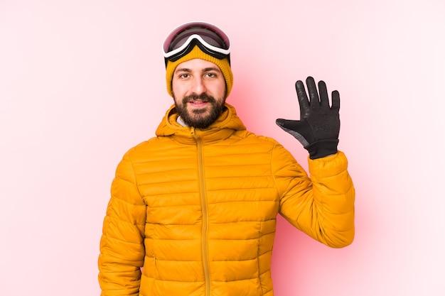 Jonge skiër man geïsoleerd glimlachend vrolijk tonend nummer vijf met vingers.