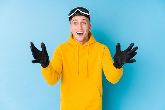 Jonge skiër man ontvangt een aangename verrassing, opgewonden en verhogen handen.