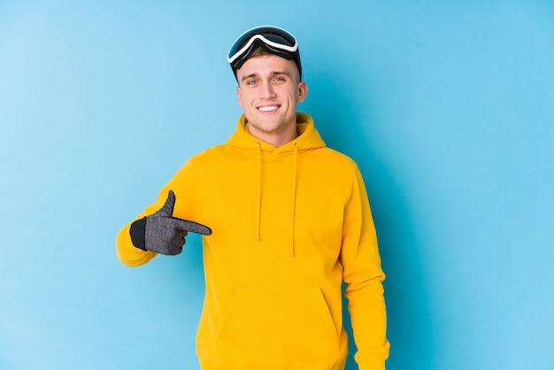 Jonge skiër man persoon wijst met de hand naar een shirt kopie ruimte, trots en zelfverzekerd