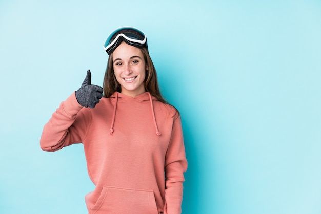 Jonge skiër vrouw geïsoleerd glimlachend en duim opheffen