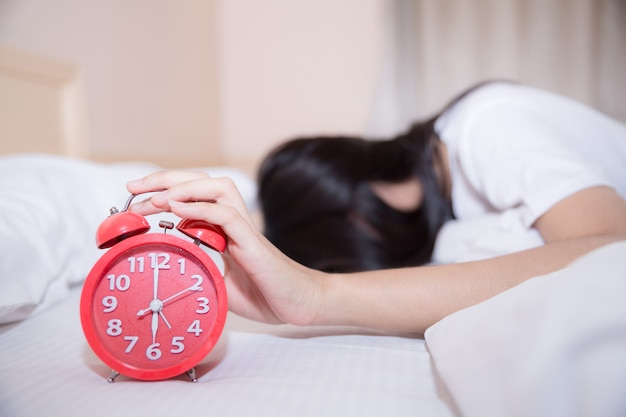 Jonge slaapvrouw en wekker in slaapkamer thuis