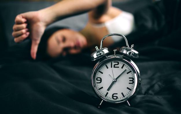 Jonge slaapvrouw en wekker thuis in slaapkamer. meisje verslapen in bed en kijken wekker in shock