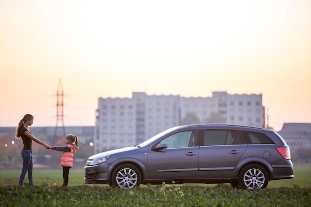 Jonge slanke aantrekkelijke langharige vrouw moeder en klein kind meisje dochter hand in hand in groene veld op zilveren auto op wazig flatgebouw en heldere hemel kopie ruimte achtergrond.