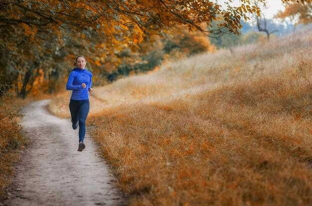 Jonge slanke athleic jogger in een zwarte sportlegging en een blauwe jas loopt langs het pad in een prachtig herfstbos.