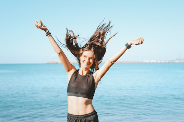 Jonge slanke atletische lange haar gelukkige vrouw in sportkleding op het overzeese strand in de ochtend