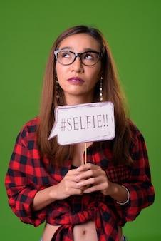 Jonge slanke aziatische vrouw tegen een groene achtergrond