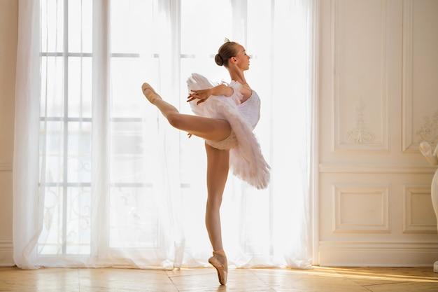 Jonge slanke ballerina in een witte tutu staat in een arabesk op pointe-schoenen in een mooie witte kamer tegenover het raam.