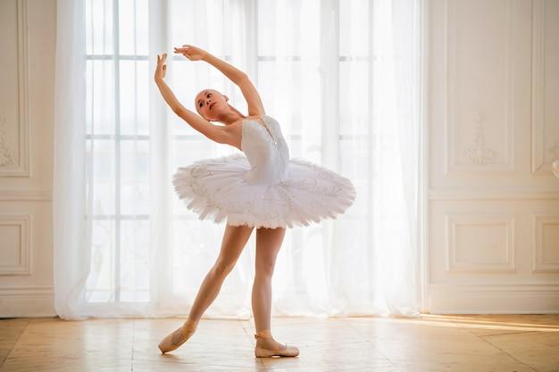 Jonge slanke ballerina in een witte tutu staat in een arabesk op pointe-schoenen in een prachtige witte kamer tegenover het raam.