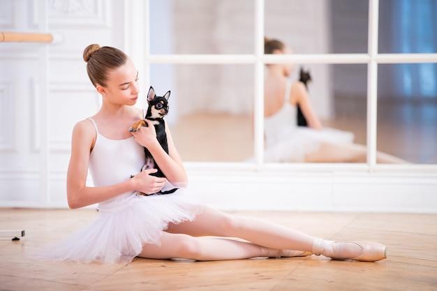 Jonge slanke ballerina in een witte tutu zittend op de vloer met kleine chihuahua hond in haar armen in mooie witte kamer voor spiegel
