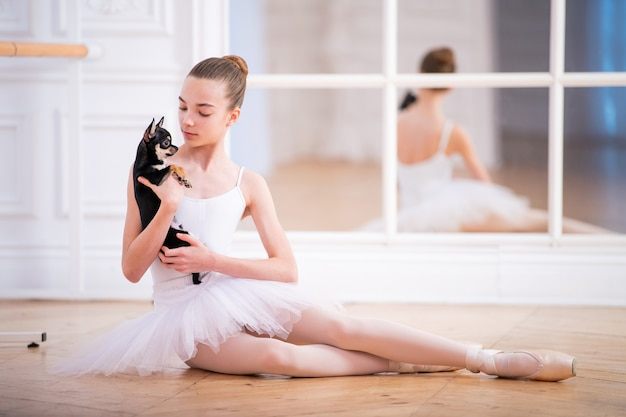 Jonge slanke ballerina in een witte tutu zittend op de vloer met kleine chihuahua in haar handen in een mooie witte kamer voor spiegel.