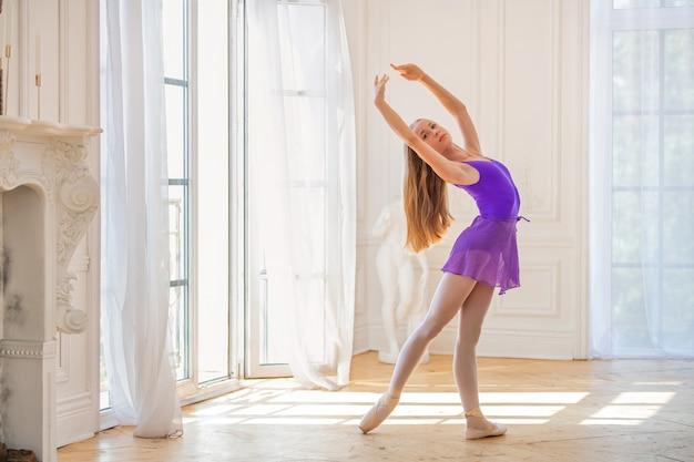 Jonge slanke ballerina in lila turnpakje staat op pointe-schoenen in een prachtige witte kamer in de buurt van een ansichtkaartraam, de wind zwaait met het gordijn.