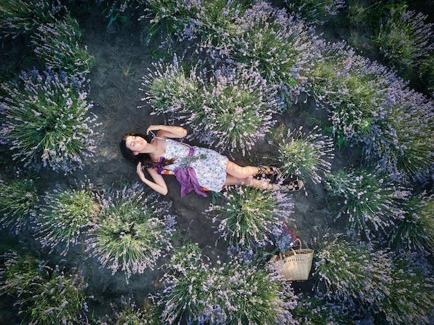 Jonge slanke blanke meisje brunette mooie ligt in lavendelveld. bovenaanzicht.