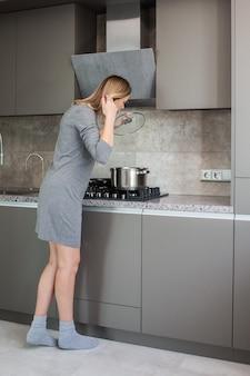 Jonge slanke blondevrouw in grijze kleding die zich door het fornuis in de moderne grijze keuken bevinden
