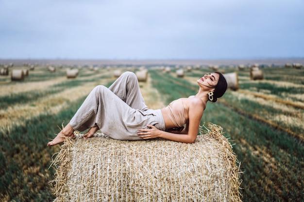 Jonge slanke brunette meisje met lichte make-up in beige top met blote buik en grijze broek, liggend op hooi, poseren, fotoshoot op veld, blauwe hemel.