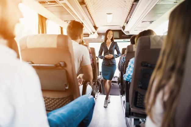 Jonge slanke busbediende en passagiers dienen.