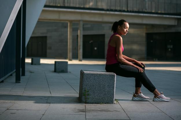 Jonge slanke dame in sportieve kleding zittend op de stenen kubus in de straat en ontspannen na de training