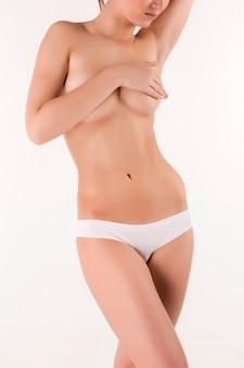 Jonge, slanke, gezonde en mooie vrouw in witte lingerie geïsoleerd op de witte achtergrond