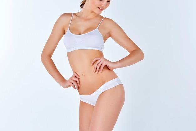 Jonge, slanke, gezonde en mooie vrouw in witte lingerie