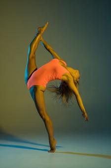 Jonge slanke meisjesturnen die acrobatische stunt doen