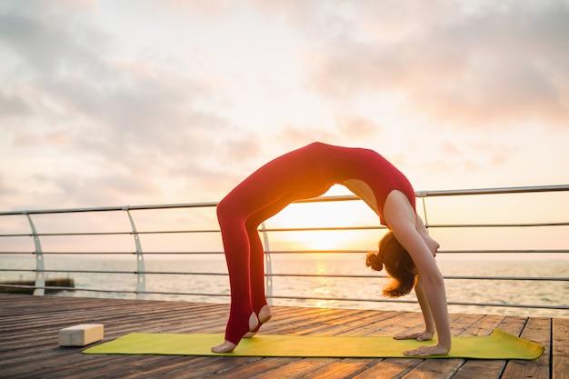Jonge slanke mooie aantrekkelijke vrouw die yoga in de ochtend op zonsopgang door overzees doet, gezonde levensstijl