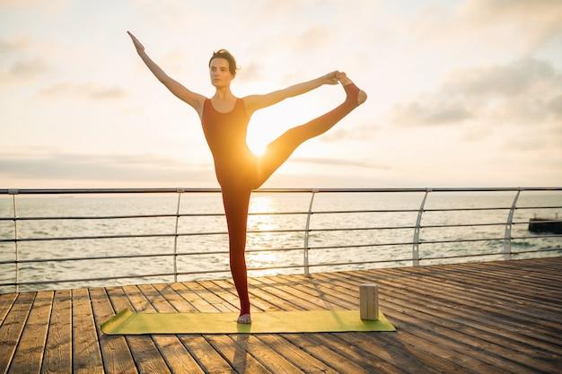 Jonge slanke mooie aantrekkelijke vrouw doet yoga in de ochtend op zonsopgang over zee, gezonde levensstijl