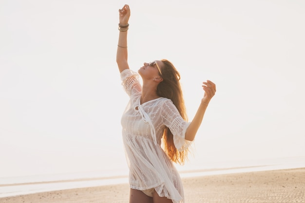 Jonge slanke mooie vrouw op zonsondergangstrand