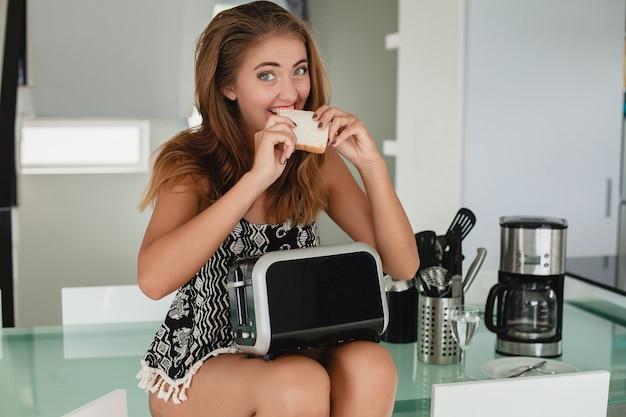 Jonge slanke mooie vrouwenzitting in keuken