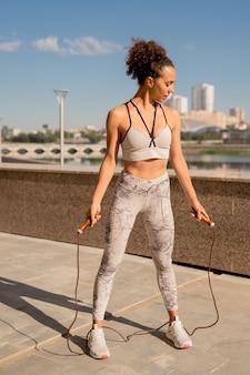 Jonge slanke sportvrouw in activewear trainen met springtouw tijdens training in stedelijke omgeving tegen rivieroever en blauwe lucht