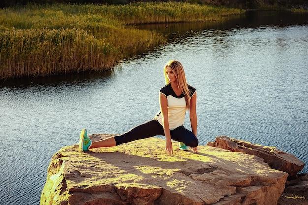 Jonge slanke vrouw beoefenen van yoga buiten op steen
