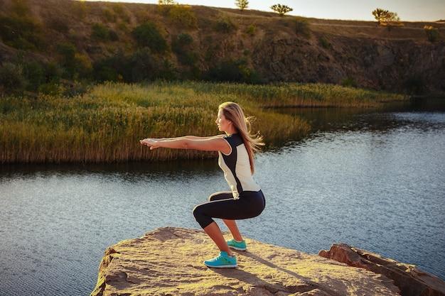 Jonge slanke vrouw beoefenen van yoga buitenshuis