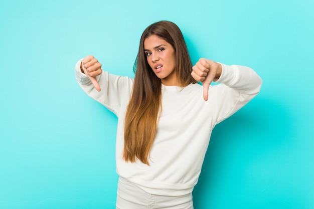 Jonge slanke vrouw die duim toont en afkeer uitdrukt.