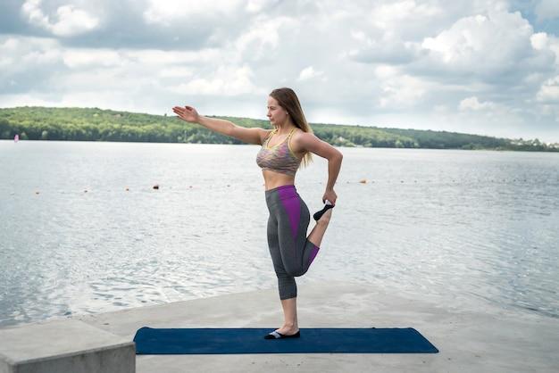 Jonge slanke vrouw die geschiktheidskleding draagt, gymnastiekoefening op yogamat dichtbij meer doet