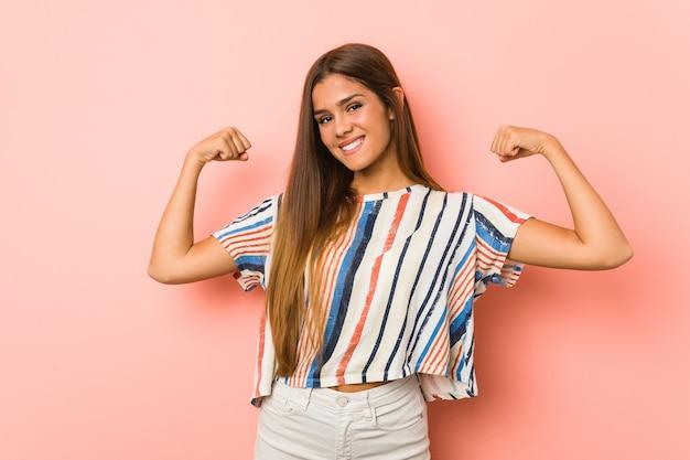 Jonge slanke vrouw die krachtgebaar met wapens toont, symbool van vrouwelijke macht