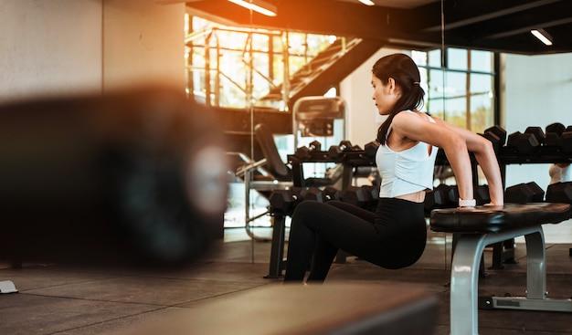 Jonge slanke vrouw die op oefenstoel uitwerkt in geschiktheidsgymnastiek