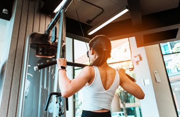 Jonge slanke vrouw die op opleidingsapparaten in geschiktheidsgymnastiek uitwerkt